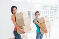 Amis féminins portant des boîtes dedans dans la nouvelle maison Image libre de droits