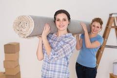 Amis féminins portant la couverture roulée après déplacement une maison Photo stock