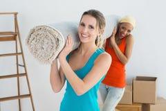 Amis féminins portant la couverture roulée après déplacement une maison Photos stock