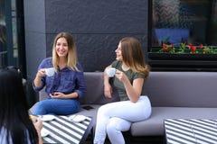 Amis féminins positifs buvant du café et s'asseyant au café Image stock