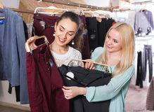 Amis féminins positifs choisissant des pantalons Photos stock