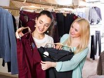Amis féminins positifs heureux choisissant des pantalons Photographie stock