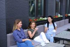 Amis féminins positifs riant du café et du bavardage, café potable Photo stock