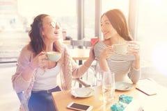Amis féminins positifs se reposant dans le café Photo libre de droits