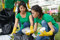 Amis féminins prenant des déchets de ménage Images stock