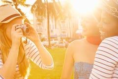 Amis féminins prenant des photographies de l'un l'autre en parc Image stock