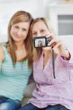 Amis féminins prenant des photos de lui-même Photographie stock libre de droits
