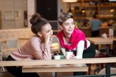 Amis féminins prenant le déjeuner au café de mail riant et souriant après l'achat photos stock