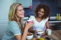 Amis féminins prenant le petit déjeuner à la table dans la cuisine Photographie stock