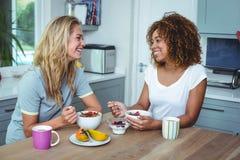 Amis féminins prenant le petit déjeuner à la table de cuisine Image libre de droits
