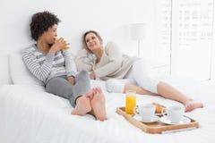 Amis féminins prenant le petit déjeuner dans le lit Photos stock