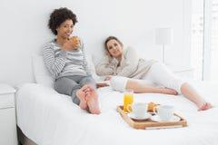 Amis féminins prenant le petit déjeuner dans le lit Photographie stock