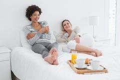 Amis féminins prenant le petit déjeuner dans le lit Photos libres de droits