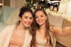 Amis féminins prenant le selfie à la maison Photos libres de droits