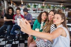 Amis féminins prenant le selfie au restaurant Photographie stock libre de droits