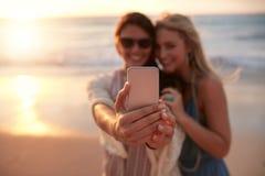 Amis féminins prenant le selfie avec le coucher du soleil de plage Images stock