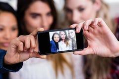 Amis féminins prenant le selfie avec le téléphone portable à la maison Photo stock