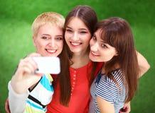 Amis féminins prenant le selfie avec le téléphone portable Photographie stock
