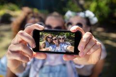 Amis féminins prenant le selfie avec le téléphone portable Image libre de droits