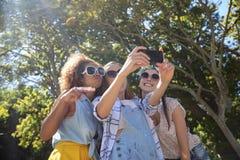 Amis féminins prenant le selfie avec le téléphone portable Images stock