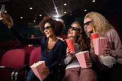 Amis féminins prenant le selfie avec le téléphone portable tout en observant le film Images libres de droits