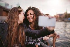 Amis féminins prenant le selfie par le lac Photos stock