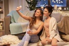 Amis féminins prenant le selfie par le smartphone à la maison Image stock