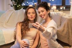 Amis féminins prenant le selfie par le smartphone à la maison Photos libres de droits