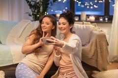 Amis féminins prenant le selfie par le smartphone à la maison Photo stock