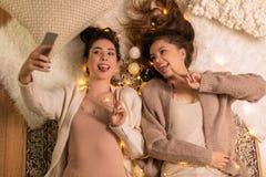 Amis féminins prenant le selfie par le smartphone à la maison Image libre de droits