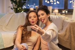 Amis féminins prenant le selfie par le smartphone à la maison Photographie stock