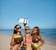 Amis féminins prenant le selfie sur la plage Images stock