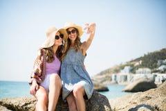 Amis féminins prenant le selfie tout en se reposant sur la roche Image stock