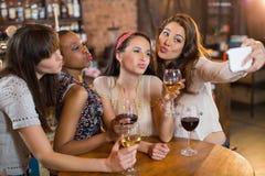 Amis féminins prenant le selfie tout en tenant des verres à vin Image libre de droits
