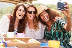 Amis féminins prenant Selfie pendant le déjeuner dehors Photos stock