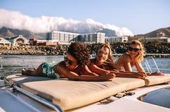 Amis féminins prenant un bain de soleil sur l'arc d'un yacht de luxe Image stock