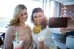Amis féminins prenant un selfie au téléphone portable Image libre de droits