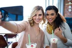 Amis féminins prenant un selfie au téléphone portable Images libres de droits