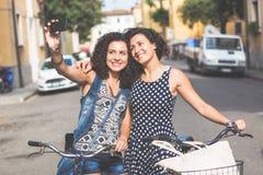 Amis féminins prenant un selfie avec leurs bicyclettes Images libres de droits