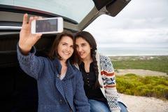 Amis féminins prenant un selfie tandis que sur une promenade en voiture ensemble Images stock