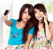 Amis féminins prenant une photo de lui-même Photo stock