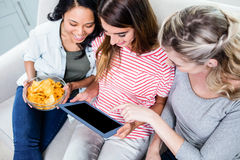 Amis féminins regardant dans le comprimé numérique tout en ayant des casse-croûte Images libres de droits