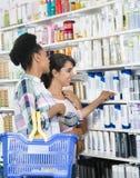 Amis féminins regardant des produits dans la pharmacie Images libres de droits