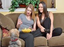 Amis féminins regardant la TV avec le chien Images stock