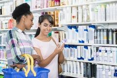 Amis féminins regardant le produit dans la pharmacie Image libre de droits