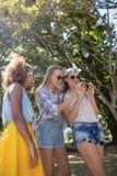 Amis féminins regardant le téléphone portable en parc Photo libre de droits