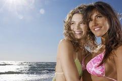 Amis féminins regardant loin la plage Images libres de droits
