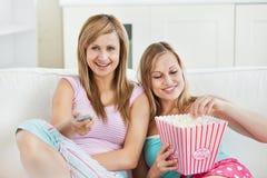 Amis féminins Relaxed mangeant du maïs éclaté regardant la TV Image libre de droits