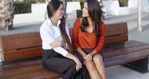 Amis féminins reposant la causerie dans une place urbaine Photo stock