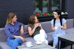 Amis féminins riant et parlant au café Photographie stock libre de droits